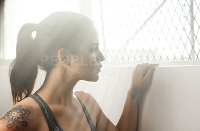 Buy stock photo Cropped shot of a young female athlete looking thoughtful at the gym