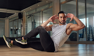 Buy stock photo Full length shot of a handsome young male athlete doing crunches in the gym