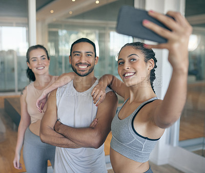 Buy stock photo Shot of three young athletes taking a selfie while standing together in the gym