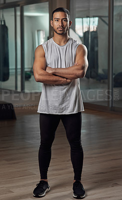 Buy stock photo Full length portrait of a handsome young male athlete standing with his arms crossed in the gym