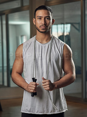 Buy stock photo Cropped portrait of a handsome young male athlete standing with a skipping rope in the gym