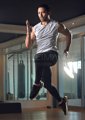 Buy stock photo Full length shot of a handsome young male athlete jumping during his workout in the gym