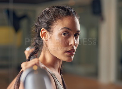 Buy stock photo Cropped portrait of an attractive young female athlete working out with weights in the gym