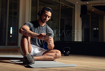 Buy stock photo Full length shot of a handsome young male athlete checking his phone while sitting in the gym