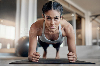 Buy stock photo Full length portrait of an attractive young female athlete planking in the gym