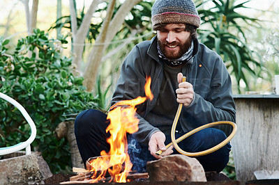 Buy stock photo Shot of a young man lighting a fire in preparation for a barbecue