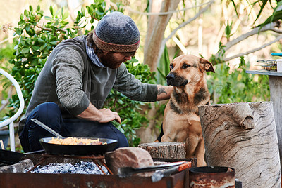 Buy stock photo Shot of a young man having a barbecue in the backyard with his dog