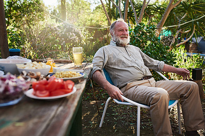 Buy stock photo Shot of a senior man having a relaxing barbecue in his backyard at home