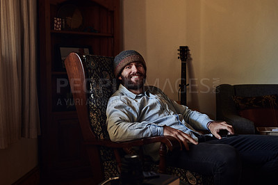 Buy stock photo Shot of a young man relaxing in a chair in the living at home