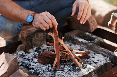 Buy stock photo Shot of an unrecognisable man lighting a fire in preparation for a barbecue