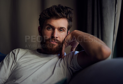 Buy stock photo Portrait of a young man relaxing on the sofa at home