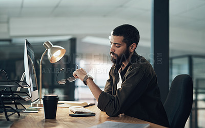 Buy stock photo Shot of a young businessman checking the time during a late night in a modern office