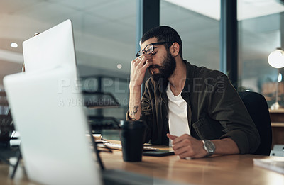 Buy stock photo Shot of a young businessman feeling stressed while working late at night in a modern office