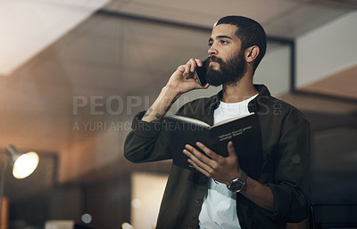 Buy stock photo Shot of a young businessman using a smartphone and reading a notebook during a late night in a modern office