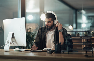 Buy stock photo Shot of a young businessman writing in a notebook and using a computer with headphones during a late night at work