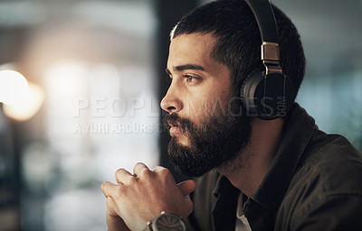 Buy stock photo Shot of a young businessman using headphones during a late night at work