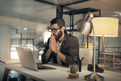 Buy stock photo Shot of a young businessman looking anxious while using a laptop during a late night at work