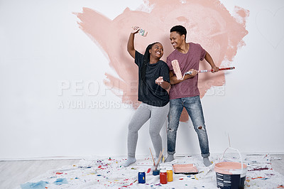 Buy stock photo Shot of a young couple painting a wall pink