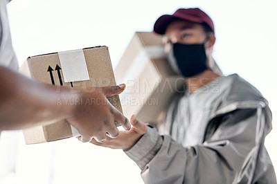 Buy stock photo Shot of a masked young man delivering a package to a customer at home