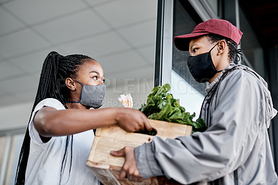 Buy stock photo Shot of a masked young man delivering fresh produce to a customer at home