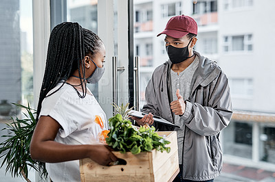 Buy stock photo Shot of a masked young man showing thumbs up while delivery fresh produce to a customer at home
