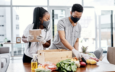 Buy stock photo Shot of a masked young couple using a digital tablet while disinfecting their groceries at home