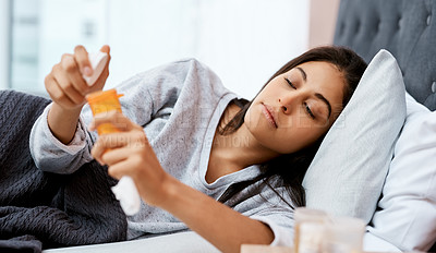 Buy stock photo Shot of a young woman taking medication while recovering from an illness in bed at home