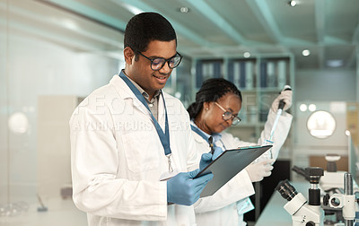 Buy stock photo Shot of a young scientist writing notes while working alongside a colleague in a lab