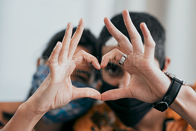 Buy stock photo Shot of a masked young couple making a heart shaped gesture with their hands at home