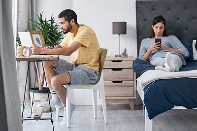 Buy stock photo Shot of a young man working from home while his wife uses a smartphone on the bed
