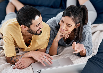 Buy stock photo Shot of a young couple using a laptop together in bed