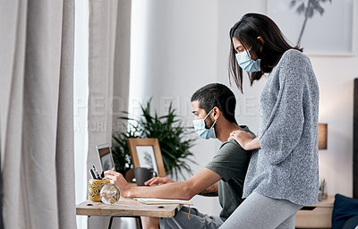 Buy stock photo Shot of a masked young couple working from home