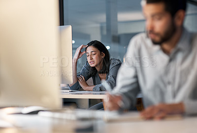 Buy stock photo Shot of a young woman feeling stressed while using a headset and computer late at night in a modern office