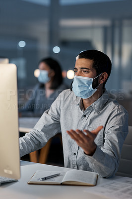 Buy stock photo Shot of a masked young man using a headset and computer late at night in a modern office