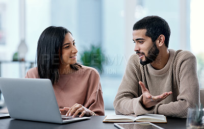 Buy stock photo Shot of a young man and woman using a laptop while working from home