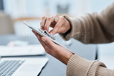 Buy stock photo Shot of an unrecognisable man disinfecting his digital tablet while working from home