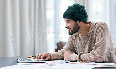 Buy stock photo Shot of a confident young man using a laptop while working from home