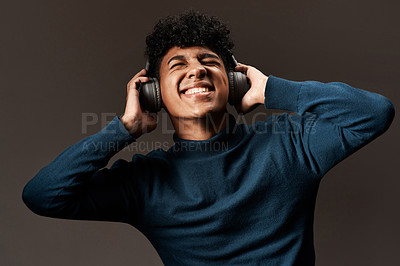 Buy stock photo Studio shot of a young man using headphones against a grey background