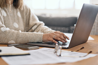 Buy stock photo Cropped shot of a woman using her laptop while working from home