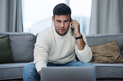 Buy stock photo Shot of a young man using a laptop and smartphone while working from home