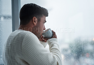 Buy stock photo Shot of a young man having coffee and looking out of a window on a rainy day at home