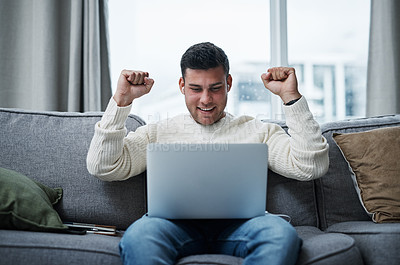 Buy stock photo Shot of a young man cheering while using a laptop on the sofa at home