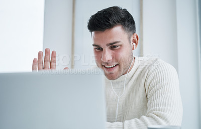 Buy stock photo Shot of a young man using a laptop to make a video call while working from home