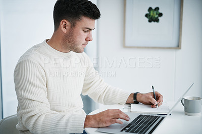 Buy stock photo Shot of a young man using a laptop and writing in a notebook while working from home