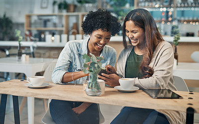 Buy stock photo Shot of two friends looking at something on a cellphone while sitting together in a coffee shop