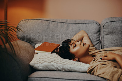 Buy stock photo Shot of a beautiful young woman taking a nap after reading a book