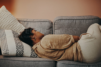 Buy stock photo Shot of a young woman taking a nap on the sofa at home