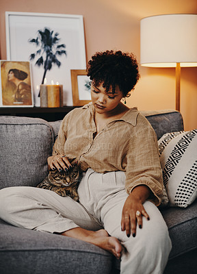 Buy stock photo Shot of a young woman relaxing at home with her cat