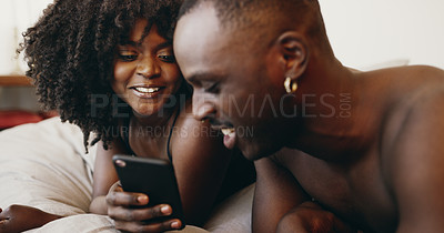 Buy stock photo Shot of a young couple using a smartphone together in bed at home