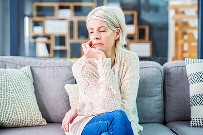 Buy stock photo Shot of a senior woman looking sad on the sofa at home